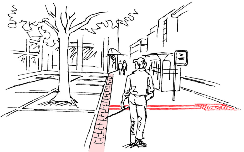 Blinde Person ertastet sich entlang einer Rinne auf einer Fussgängerfläche